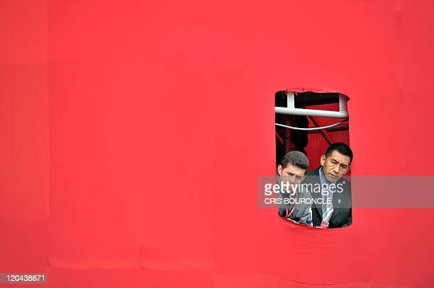 Security officers to Peruvian President Ollanta Humala and his wife Nadine Heredia observe from a cutout in a gigantic flag panel as the newly...