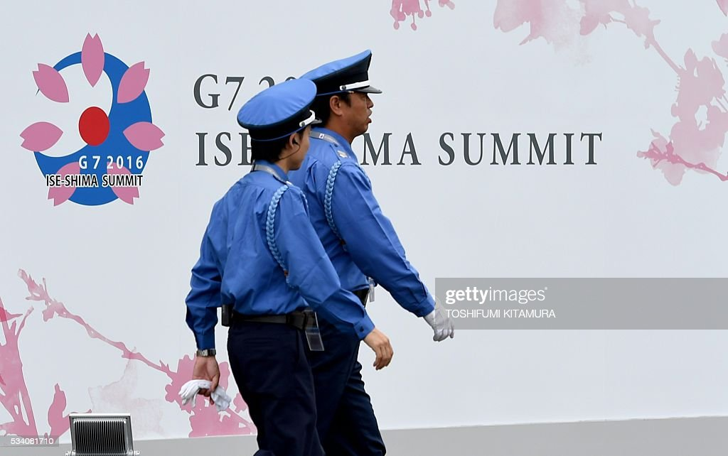 Security officers walk past the Group of Seven (G7) summit logo at the International Media Centre in Ise city, Mie prefecture on May 25, 2016. Japan is on high-alert ahead of a Group of Seven summit with thousands of police on the streets of Tokyo and fanning out across the country as authorities boost security to unprecedented levels. / AFP / TOSHIFUMI