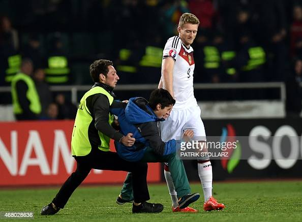 A security official detains a man on the field in front of Germany's midfielder Andre Schuerrle after the Euro 2016 qualifying football match between...