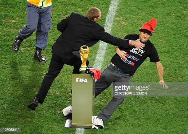 A security official tries to avoid a supporter from reaching the FIFA World Cup trophy aftre it was presented by the captain of the Italian national...