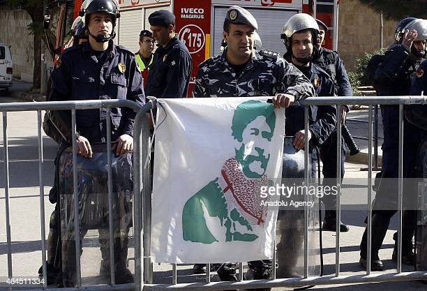 Security officials stand guard as supporters of Lebanese Georges Ibrahim Abdullah who has been jailed in France chants slogans during a protest in...