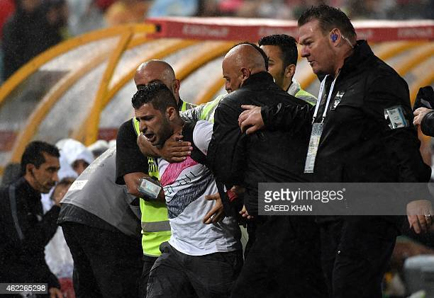 Security officials take away a pitch invader during the semifinal football match between South Korea and Iraq at the AFC Asian Cup in Sydney on...