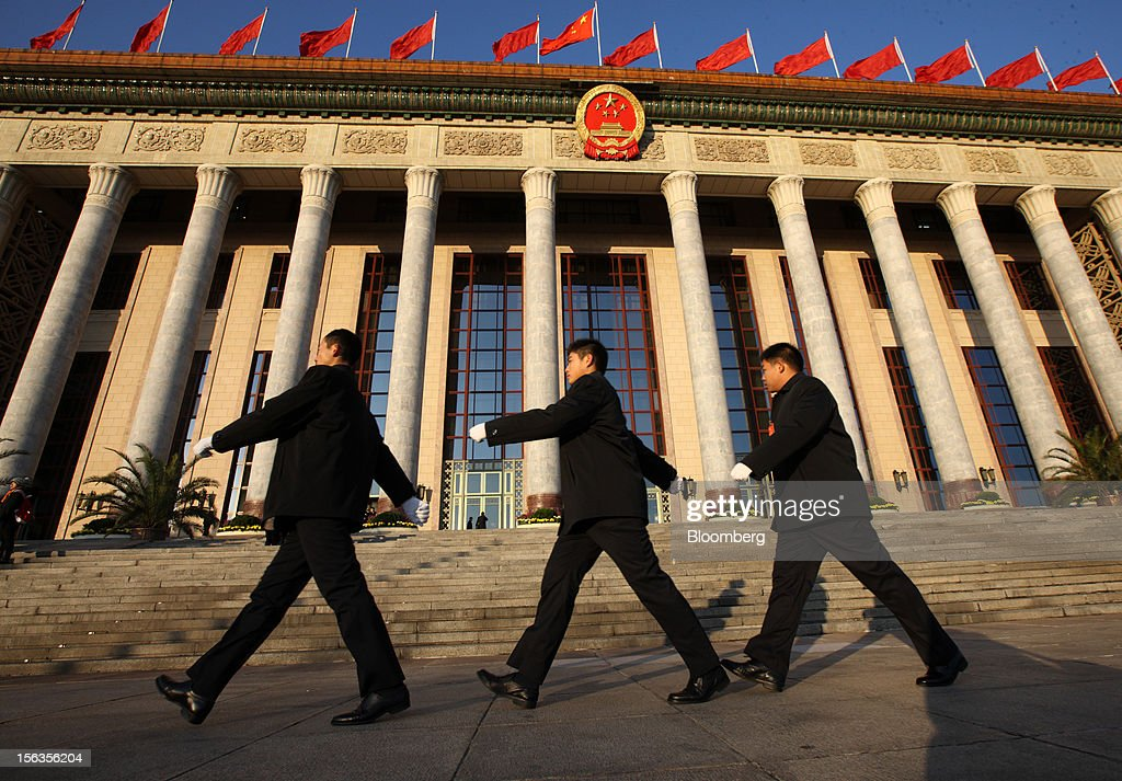 Security officials walk past the Great Hall of the People before the closing session of the 18th National Congress of the Communist Party of China in Beijing, China, on Wednesday, Nov. 14, 2012. Vice President Xi Jinping and Vice Premier Li Keqiang were reappointed to the Chinese Communist Party's Central Committee, positioning them to take over the top two posts in the world's second-biggest economy. Photographer: Tomohiro Ohsumi/Bloomberg via Getty Images