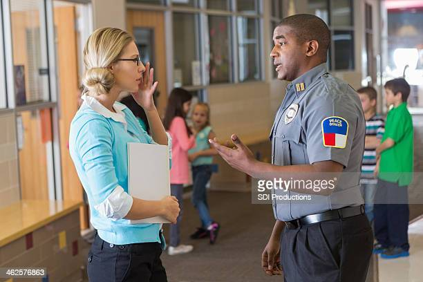 Security or police officer talking with elementary school teacher