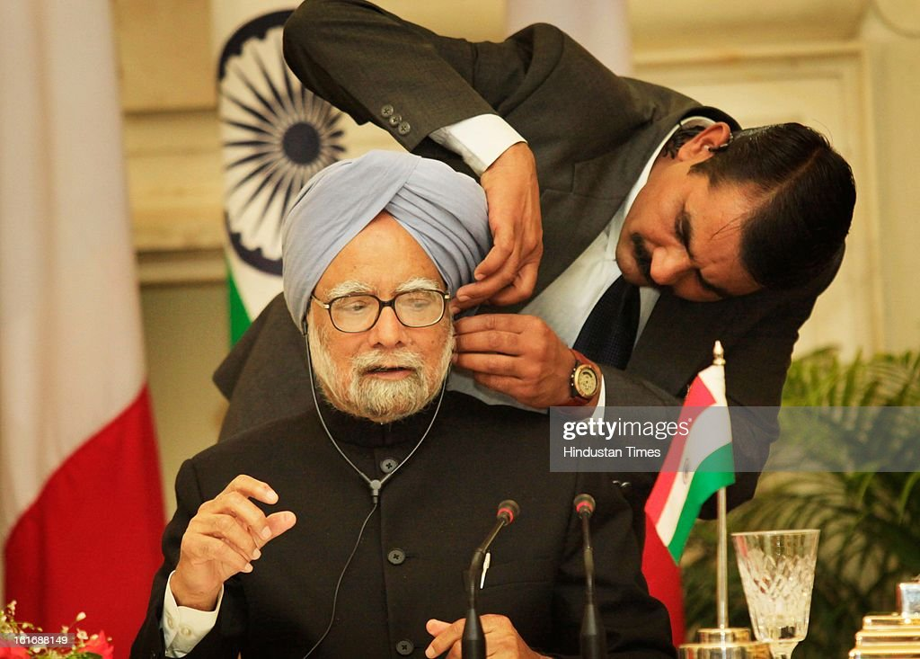 A security person assists Indian Prime Minister Manmohan Singh to wear an ear phone as he sits with French President Francois Hollande, unseen, during signing of agreements on February 14, 2013 in New Delhi, India.