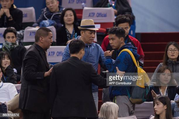 Security personel removes a man after he and another interupted the game of Rafael Nadal of Spain men's quarterfinals singles match against Grigor...