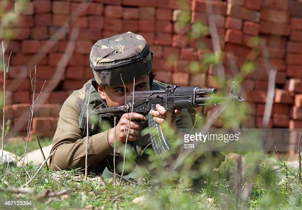 A security personel stays alert in position during an encounter between security forces and armed militants at Mehasar village in Samba sector some...