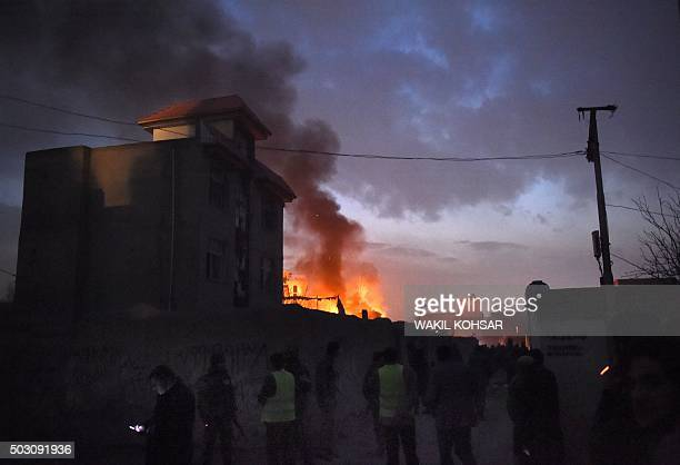 Security personnel and bystanders look on as flames and smoke rise at the site of a suicide car bomb attack at a French restaurant Le Jardin in Kabul...