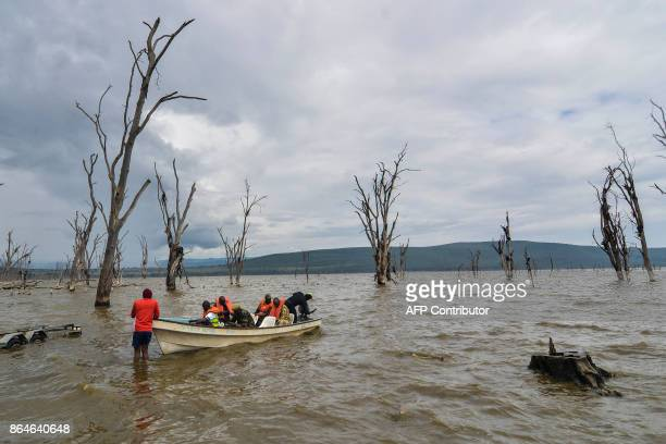 Security personnel and volunteer divers prepare to leave on a boat on a search mission for a helicopter that crashed into Lake Nakuru early on...