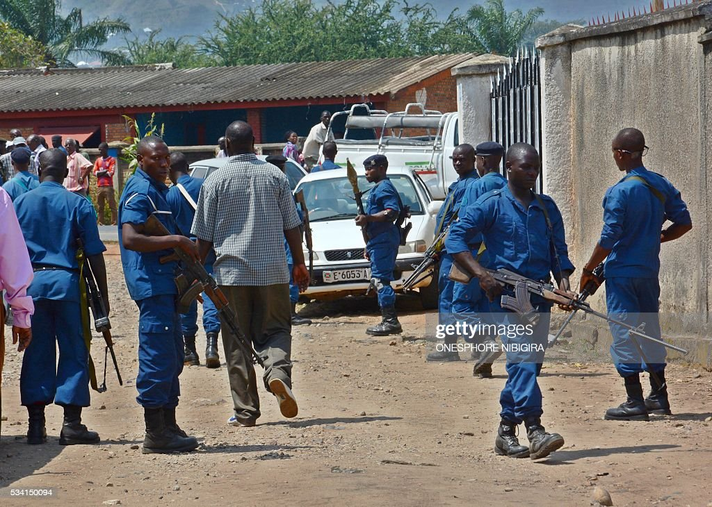 Security personnel block the area close to where the body of Col. (Rtd) Lucien Rufyiri lies on May 25, 2015 in the Burundian capital, Bujumbura after he was gunned down by unidentified gunmen as he arrived at his residence. The Tutsi colonel who has been retired for several years was killed outside his home in a rebellious district of Bujumbura 'by armed criminals', according to a source within the family. 'Colonel Lucien Rufyiri has been murdered this morning in front of his house and a son who was with him was injured,' he told AFP a family member, who requested anonymity. / AFP / ONESPHORE