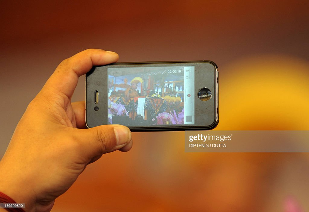 A security personnel captures video using his cellphone of Tibetan Spiritual Leader The Dalai Lama during the seventh day of the Kalachakra Festival in Bodhgaya on January 7, 2012. Kalachakra 2012, a festival of teachings and meditations will take place from January 1, 2012 for ten days in the northern Indian state of Bihar and will be attended by Tibetan Spiritual Leader The Dalai Lama. AFP PHOTO/Diptendu DUTTA