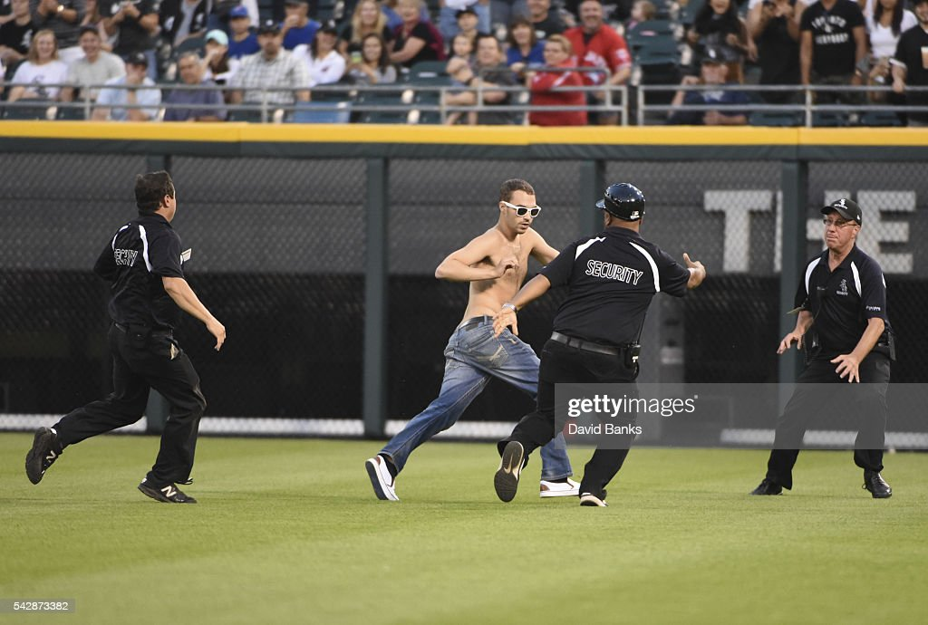 Security personnel chase a fan who ran onto the field during the fourth inning of a game between the Chicago White Sox and the Toronto Blue Jays on June 24, 2016 at U. S. Cellular Field in Chicago, Illinois.