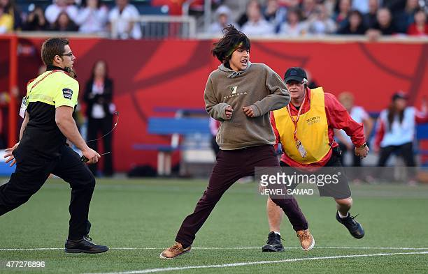 Security personnel chase a man as he run in the field of play during the Group A football match of the 2015 FIFA Women's World Cup between China and...