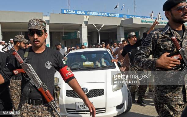 Security personnel escort a vehicle carrying Pakistani cricketer Fakhar Zaman following his arrival from London outside the Bacha Khan International...