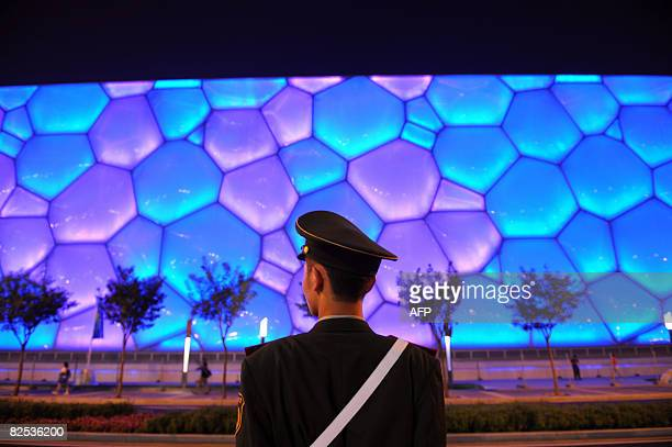 Security personnel guard looks at the National Aquatics Center as he stands guard near the National Stadium also know as the 'Bird's Nest' in Beijing...