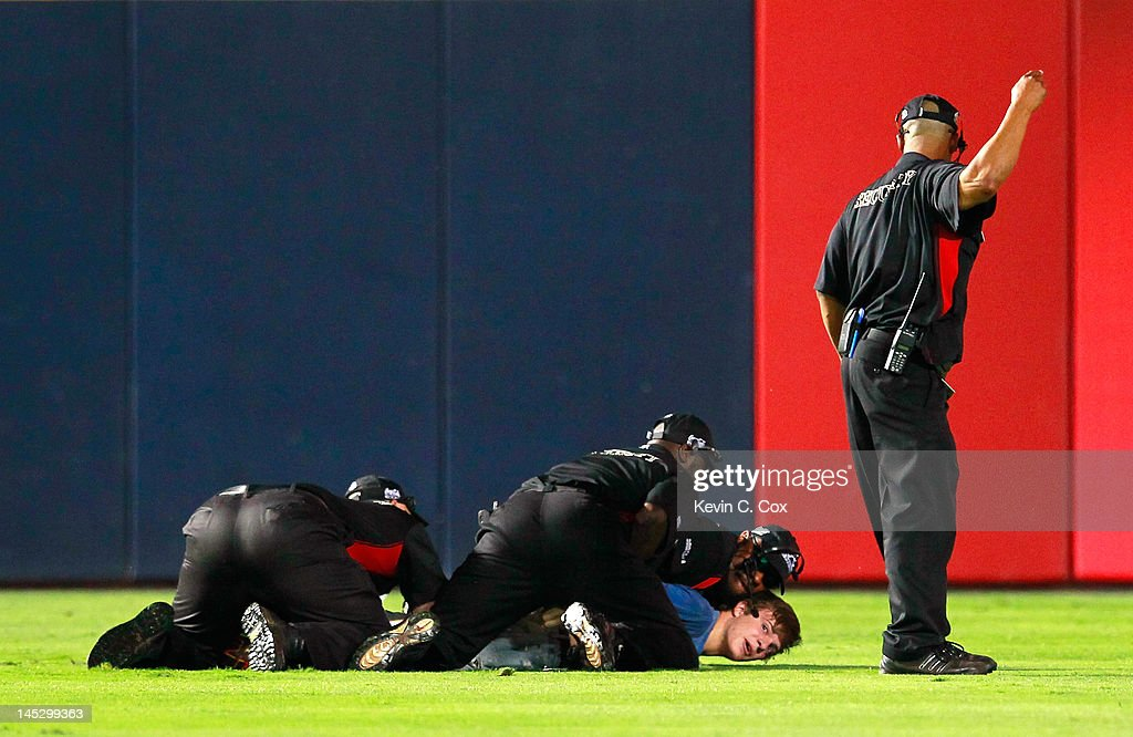 Security personnel holds down a fan who rushed the field in the ninth inning of the game between the Atlanta Braves and the Washington Nationals at Turner Field on May 25, 2012 in Atlanta, Georgia.