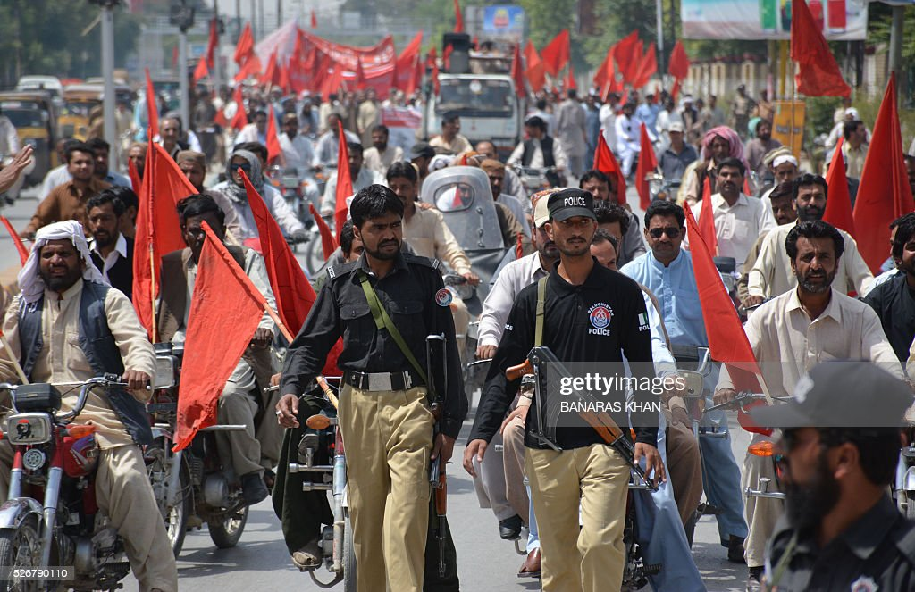Security personnel look on as Pakistani labourers shout slogans and wave placards as they march behind banners at a rally in Quetta on May 1, 2016, on International Labour Day or May Day. / AFP / BANARAS