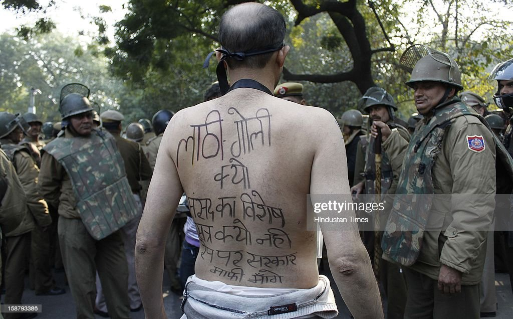 Security personnel looking at an anti-rape protester displaying a message on his back during a demonstration to mourn the death of the gang-rape victim at Jantar Mantar on December 29, 2012 in New Delhi, India. The nation was shocked in the morning as she was declared dead at the Singapore's Mount Elizabeth Hospital, where she was undergoing treatment. The Gang-rape of 23 year old girl in a moving bus enraged the entire country and galvanized people to demand for protection for women and justice for victims of such heinous crimes. There was heavy security deployment all around the city as many roads were blocked and metro stations were closed down to avoid any untoward incident.