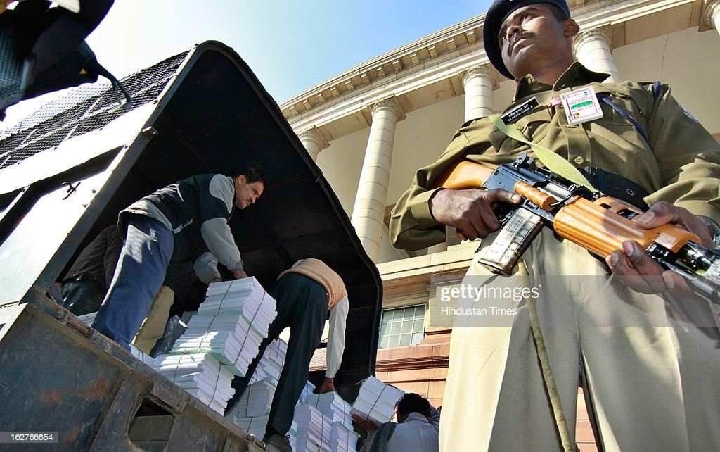 Security personnel on high alert as workers unload the budget papers at Parliament as Railway minister present the Indian Railway budget 2013-14, on February 26, 2013 in New Delhi, India.