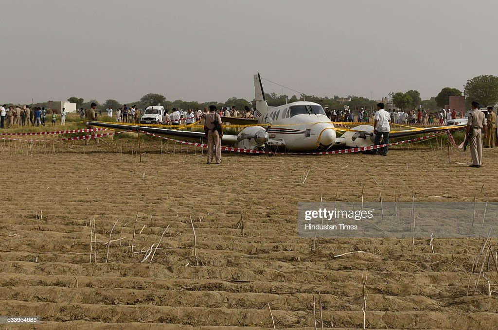 Security personnel secure the site where an air-ambulance crash landed at Village Kair in Nazafgarhon May 24, 2016 in New Delhi, India. An air ambulance coming from Patna with a patient, who had suffered a brain stroke, and six others on board crash landed in Najafgarh area of South West Delhi after both its engines shut down one after the other but all passengers escaped unhurt.