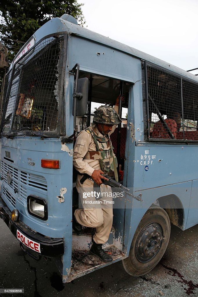 Security personnel stand guard near a damaged bus that was attacked by militants in Pampore, on the outskirts of Srinagar, on June 25, 2016 in Srinagar, India. Eight Central Reserve Police Force men were killed and 20 others injured after militants ambushed a convoy of the security force on the Srinagar-Jammu national highway in Jammu and Kashmir's Pulwama district. Two militants were also killed in the gunfight, the second major attack on a security convoy this month.