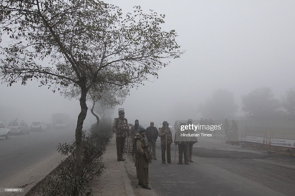 Security personnel stand guard outside the cremation ground during the funeral of Gang Rape victim after her body arrived from Singapore on December 30, 2012 in New Delhi, India. The 23 year girl died on Saturday at hospital in Singapore, trigging nationwide public outrage. She was gang raped in moving bus on the night of December 16, 2012 in Delhi.