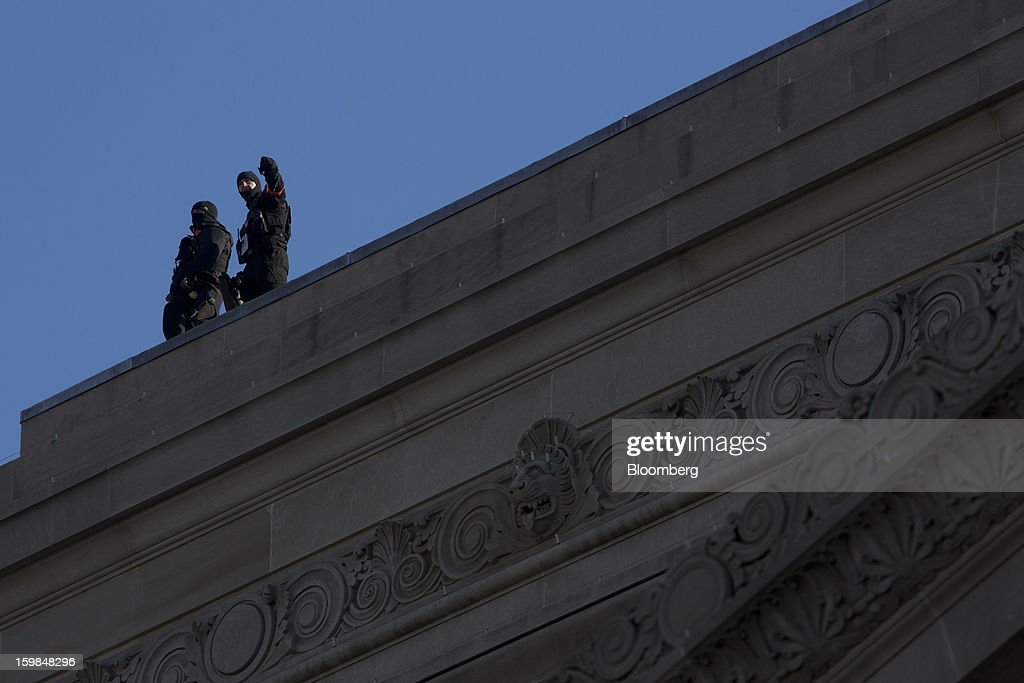 Security personnel stand on top of a building along the parade route during the U.S. presidential inauguration in Washington, D.C., U.S., on Monday, Jan. 21, 2013. A crowd estimated by police to be as large as 700,000, including warmly dressed women with American flags stuck in their hair, a smattering of celebrities and many Republicans, gathered today to witness President Barack Obama take his second oath of office on the steps of the U.S. Capitol. Photographer: Victor J. Blue/Bloomberg via Getty Images
