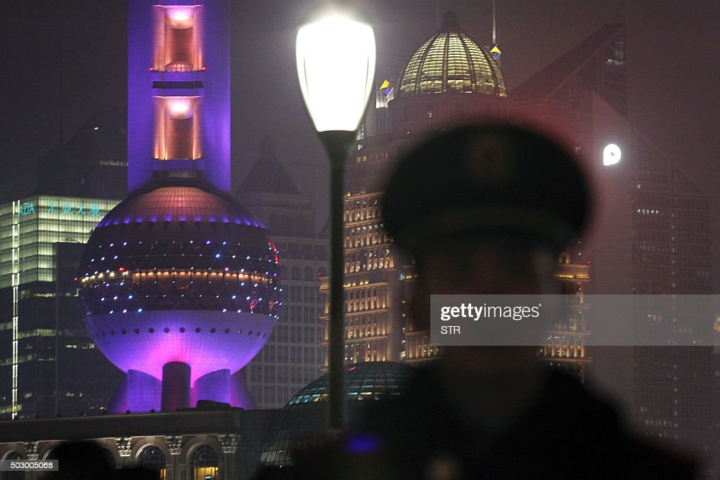 A security personnel stands on patrol on New Year's eve on the historic riverfront known as 'the Bund' in Shanghai on December 31 2015 China's...
