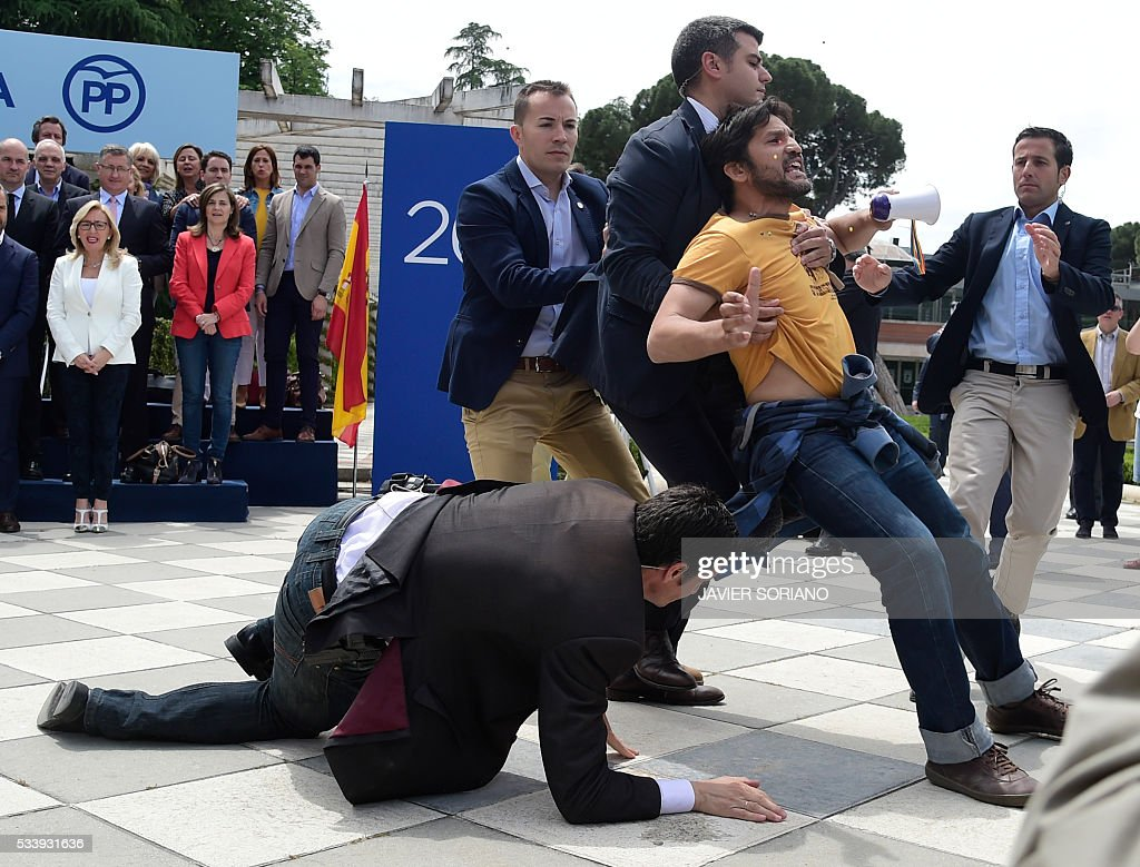Security personnel subdue a man protesting during the presentation of the Spanish Congress' Popular Party (PP) candidates for the June 26 upcoming general election in Madrid on May 24, 2016. / AFP / JAVIER