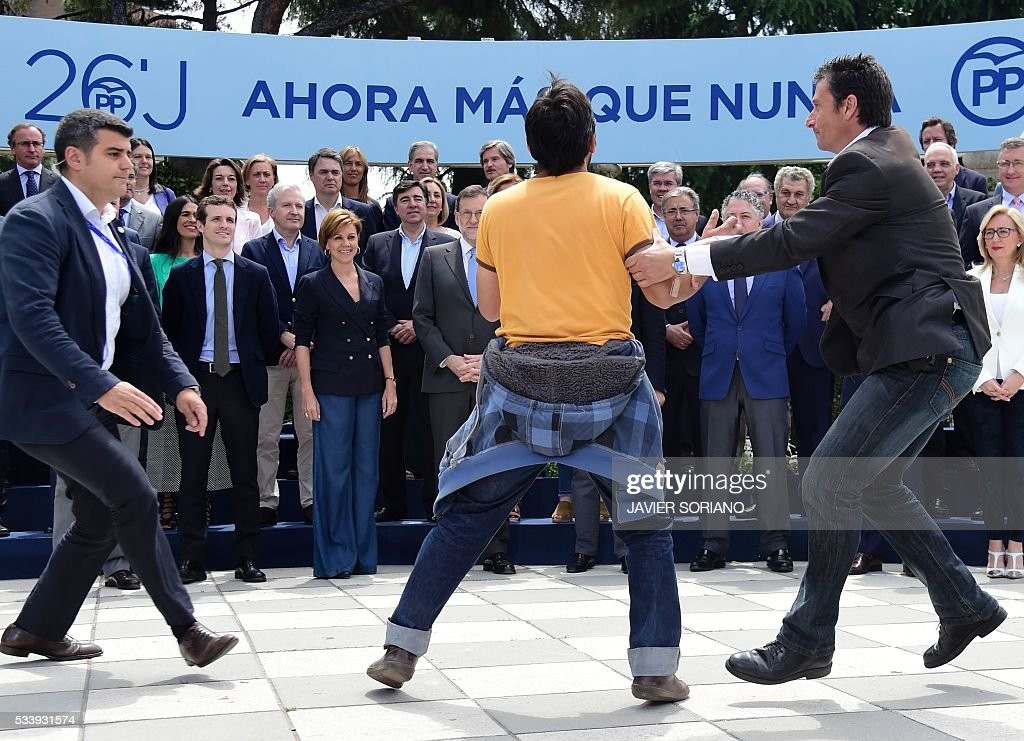 Security personnel subdue a man protesting in front of Spanish acting Prime Minister and Popular Party (PP) President Mariano Rajoy (C) during the presentation of the Spanish Congress' candidates for the June 26 upcoming general election in Madrid on May 24, 2016. / AFP / JAVIER