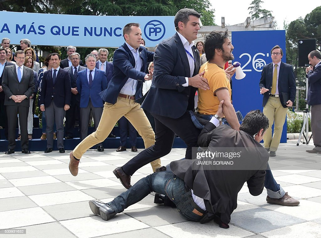 Security personnel subdue a man protesting in front of Spanish acting Prime Minister and Popular Party (PP) President Mariano Rajoy (L) during the presentation of the Spanish Congress' PP candidates for the June 26 upcoming general election in Madrid on May 24, 2016. / AFP / JAVIER
