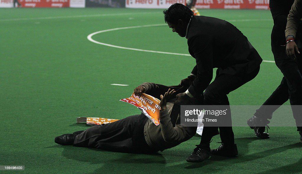 Security personnel taking out two people who were protesting against Pakistan troops' brutal killing of India soldiers, while the first match of Hockey India League is in progress between Delhi Waveriders and Punjab Warriors at Major Dhyan Chand Stadium on January 14, 2013 in New Delhi, India. Hockey India League is a professional league for field hockey competition comprising five franchisee-based teams consisting of players from India and around the world. The entire event takes place on home and away basis culminating into multi header playoffs.
