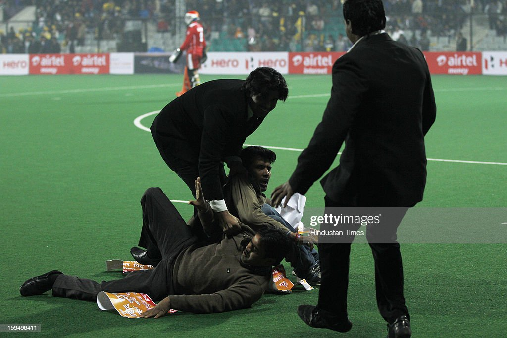 Security personnel taking out two people who were protesting against Pakistan troops' brutal killing of Indian soldiers, while the first match of Hockey India League is in progress between Delhi Waveriders and Punjab Warriors at Major Dhyan Chand Stadium on January 14, 2013 in New Delhi, India. Hockey India League is a professional league for field hockey competition comprising five franchisee-based teams consisting of players from India and around the world. The entire event takes place on home and away basis culminating into multi header playoffs.