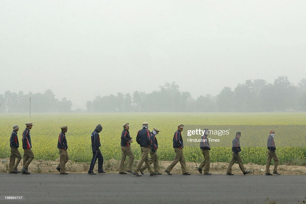 Security personnel walks past the Mustard fields as dense fog engulf the area around Dwarka as Mercury dips further below to 3 degree in Morning on January 4, 2013 in New Delhi, India. Dense fog has affected around 45 trains and 22 flights.