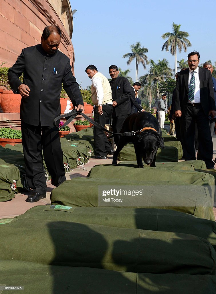 Security personnel with sniffer dog checking sacks containing the 2013-14 union budget papers at the parliament house in New Delhi on Thursday.
