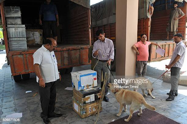 Security personnel with sniffer dogs checking boxes before loading as boxes containing official records of Jammu and Kashmir states' Civil...