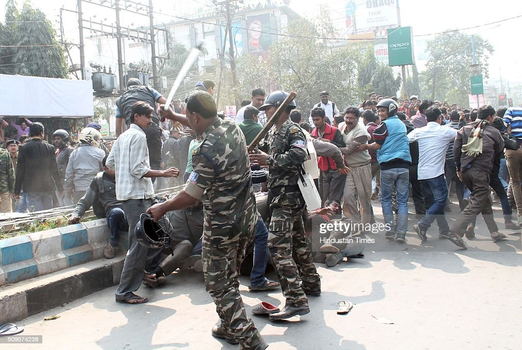 Security personnnel lathicharge to disperse the crowd as a wild elephant with a tranquilizer dart in its back side walks along busy market place on February 10, 2016 in Siliguri, India. A wild elephant had wandered from the Baikunthapur forest in Siliguri, West Bengal, crossing roads and a small river before entering the town. The panicked elephant ran amok, trampling parked cars and motorbikes before it was tranquilised.