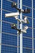 Surveillance cameras in front of a blue wall of solar cells in the sunshine.