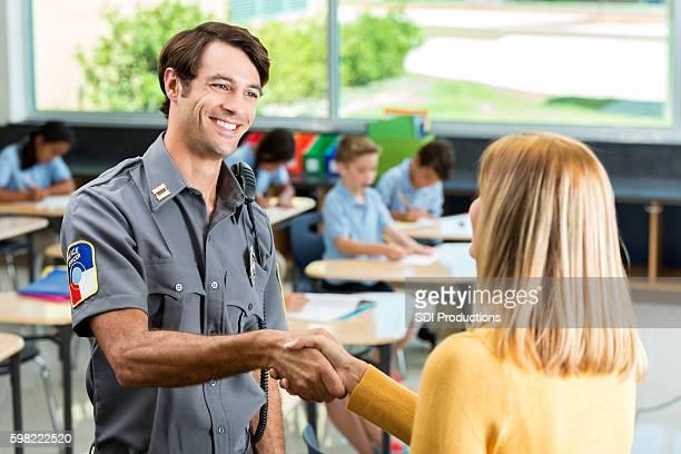 Security professional greets school teacher in classroom