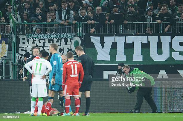 Security removes cups from the pitch during the Bundesliga match between Borussia Moenchengladbach and FC Bayern Muenchen at BorussiaPark on January...