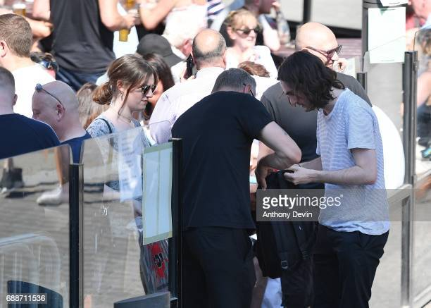 Security search bags as people enjoy the warm weather outside Sinclair's Oyster Bar close to the Manchester Arena in central Manchester on May 26...