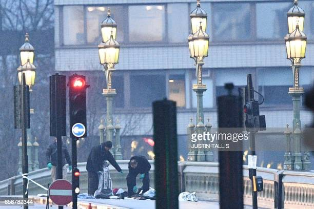 TOPSHOT Security services staff pick through debris including a car number plate left following the March 22 terror attack on Westminster Bridge in...