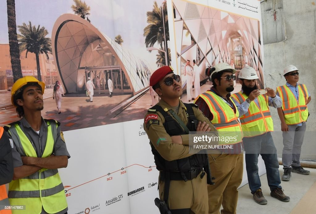 Security staff and workers stand in front of a giant poster on May 4, 2016 at a construction site of a section of the Saudi capital Riyadh's $22.5 billion metro system. The system, which will have six lines covering 176 kilometres (109 miles), supported by a bus network of 1,150 kilometres, is due to be completed by the end of 2018. Deputy Crown Prince Mohammed bin Salman announced a long-term reform programme, dubbed 'Vision 2030', marking the beginning of a hugely ambitious attempt to move Saudi Arabia beyond oil, the backbone of its economy for decades. / AFP / FAYEZ