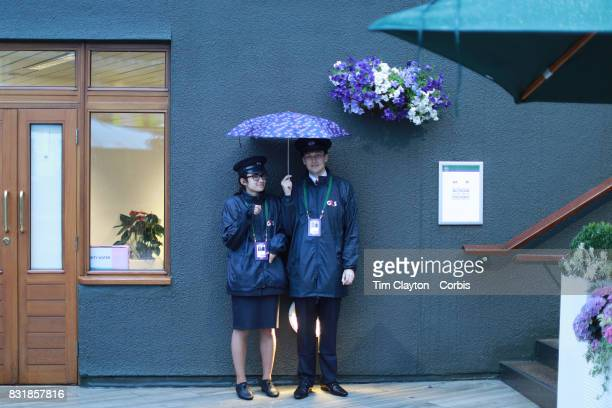 Security staff during a rain shower during the Wimbledon Lawn Tennis Championships at the All England Lawn Tennis and Croquet Club at Wimbledon on...