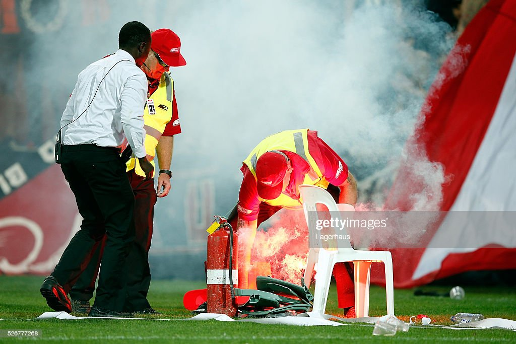 Security staff extinguish a flare during the 2015/16 A-League Grand Final match between Adelaide United and the Western Sydney Wanderers at Adelaide Oval on May 1, 2016 in Adelaide, Australia.