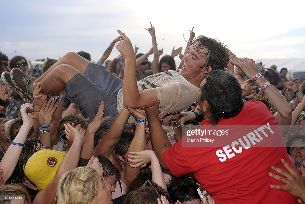 Security staff pull a crowd surfer from the front rows of the audience in the mosh pit at the Pyramid Rock Festival on 31st December 2009 in Phillip Island, Australia.