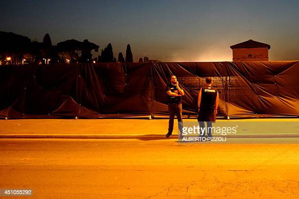 Security staff stand outside the visual barrier erected around the Rolling Stones concert area in Circus Maximus in Rome on June 22 2014 About...