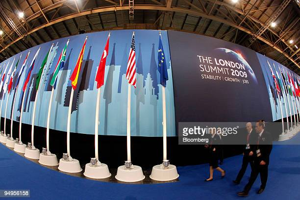 Security staff walk past the flags of the G20 in the media centre at the G20 London summit in London UK on Thursday April 2 2009 UK World leaders...