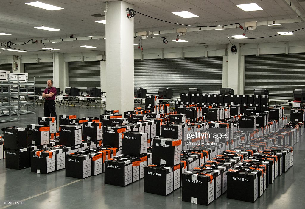 Security stands next to a stack of ballot boxes ready to be opened during the London Mayoral and Assembly election count at Kensington Olympia on May 6, 2016 in London, England. This is the fifth mayoral election since the position was created in 2000. Previous London Mayors are Ken Livingstone for Labour and more recently Boris Johnson for the Conservatives. The main candidates for 2016 are Sadiq Khan, Labour, Zac Goldsmith, Conservative, Sian Berry, Green, Caroline Pidgeon, Liberal Democrat, George Galloway, Respect, Peter Whittle, UKIP and Sophie Walker, Wonmen's Equality Party.