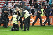 Security stewards tend to an injured colleague as riot policemen take position to secure the access from the pitch to the players' locker rooms after...